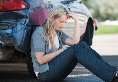 Lady sitting on the ground by her car after an personal injury accident